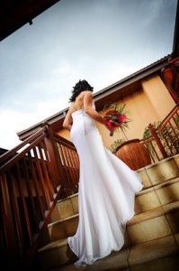 Bride on stairs with red roses